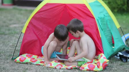 quintal : Two boys, playing on tablet in a tent in the backyard, summertime