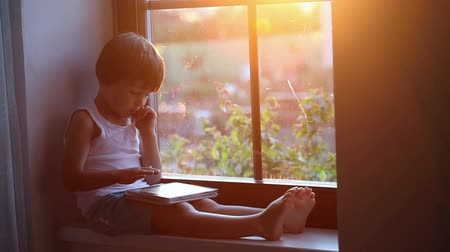 menino : Sweet little boy, playing on tablet, sitting on a window shield, sunset behind the window
