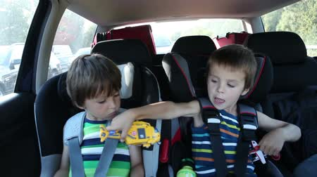 ülés : Happy little boys playing game on tablet and playing with toys, while sitting in child safety seat in the car