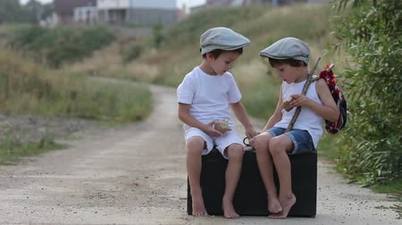 kufr : Two boys, sitting on a big old vintage suitcase, playing with toys and eating bread