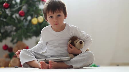 majom : Cute little boy and his monkey toy, playing on tablet