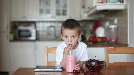 turmix : Happy school boy drinking  healthy smoothie as a snack at home, eating cherries and playing on tablet, sitting around the table