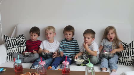 сидеть : Five sweet kids, friends, sitting in living room at home, watching TV and eating popcorn Стоковые видеозаписи