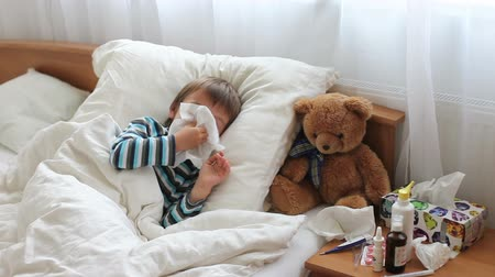 doente : Sick child boy lying in bed with a fever,resting, coughing and blowing his nose