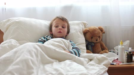 horečka : Sick child boy lying in bed with a fever,resting, coughing and blowing his nose