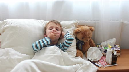 грипп : Sick child boy lying in bed with a fever,resting, coughing and blowing his nose