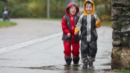 bahno : Two boys, brothers, jumping in muddy puddle in the park, autumn time on a rainy day