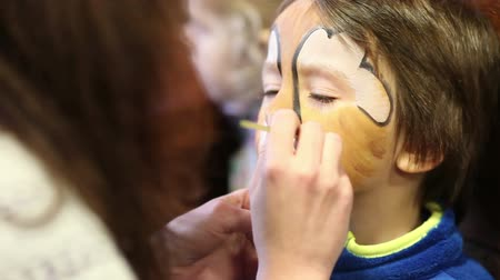 karnaval : Little boy with painted face as a lion for a carnival Stok Video