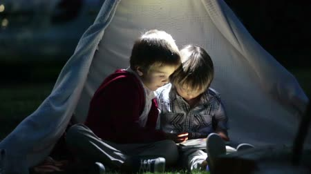 sátor : Cute little brothers, playing on tablet and telephone at night in campside, in the tent Stock mozgókép