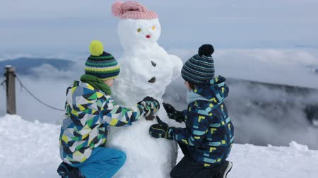 kardan adam : Two children, boy brothers, building snowman, having fun Stok Video