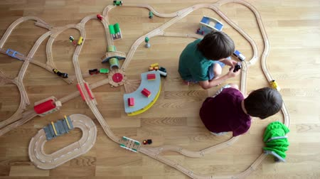 przedszkole : Sweet preschool children, boy brothers, playing with wooden railway and trains at home, top view