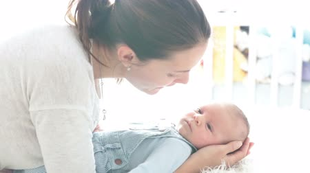 gentleness : Happy mother, talking to her newborn son, stroking and kissing him, Family concept, mom caressing newborn baby Stock Footage