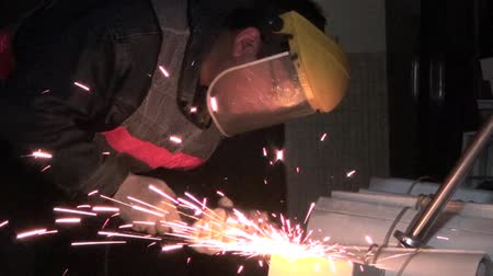metal worker : A working man in a workshop using an electric grinder