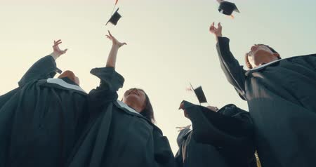 mortarboard : Graduation students in bachelor gowns throwing mortar boards up in the air