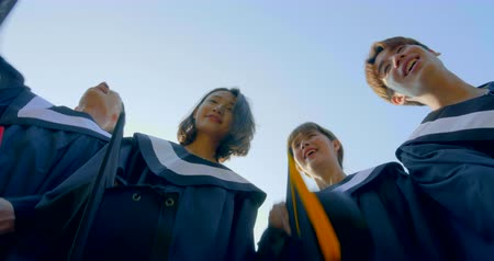 教育 : Graduation students in bachelor gowns throwing mortar boards up in the air