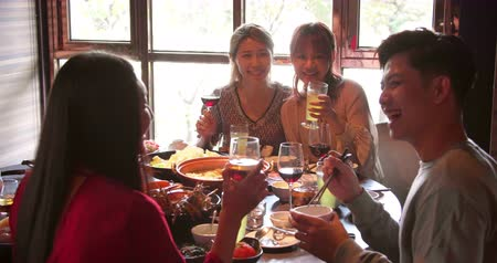 cheers : Happy young friends enjoy dinner in hot pot restaurant