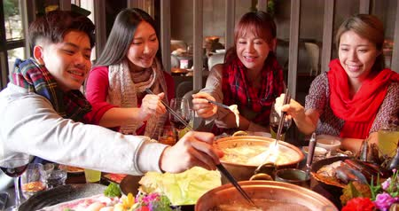 cin cin : Happy young friends enjoy dinner in hot pot restaurant