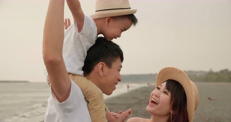 tendo : happy asian family having fun on the beach