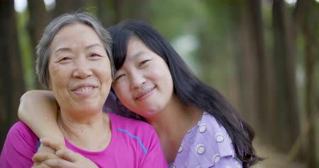 Cheerful mature woman embracing senior mother
