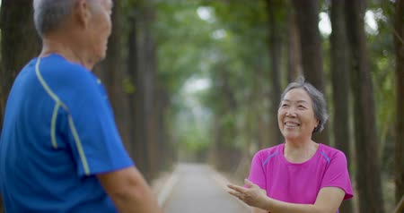 senior lifestyle : Senior Couple doing stretching on the forest road Stock Footage