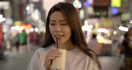 young woman enjoy bubble milk tea with street food in Night Market