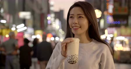 mercado : young woman enjoy bubble milk tea with street food in Night Market