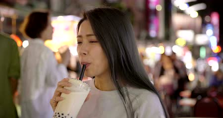 Asian woman enjoy bubble milk tea with street food in Night Market