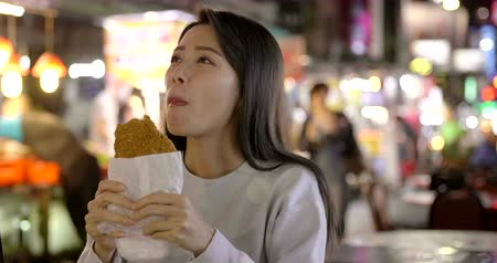 Asian woman enjoy Chicken Fillet with street food in Night Market Stok Video