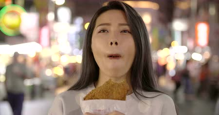 Asian woman enjoy Chicken Fillet with street food in Night Market 影像素材