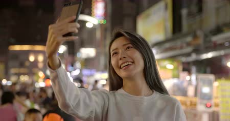 happy young asian woman using smart phone in Night Market