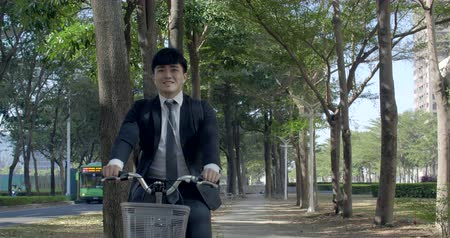 Businessman riding bicycle to work on urban street at morning
