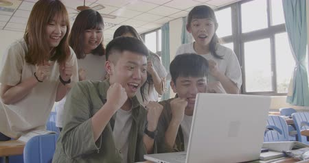 akademický : excited college students looking at laptop in classroom