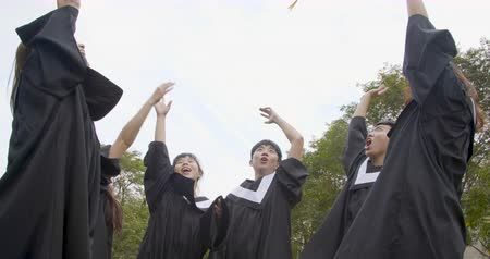 kutlama : happy students in graduation gowns holding diplomas on university campus Stok Video
