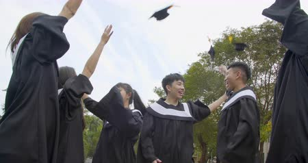 празднование : happy students in graduation gowns holding diplomas on university campus Стоковые видеозаписи
