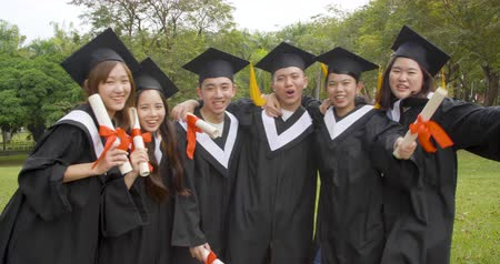 grau : happy students in graduation gowns holding diplomas on university campus Stock Footage