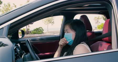 kaszel : Sick young woman wear mask and driving the car