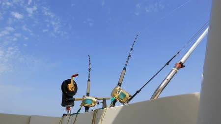 ryba : boat fishing trolling in deep blue sea with rods and reels
