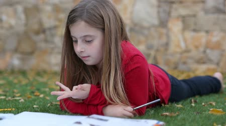 sayma : Blond kid girl maths homework laying on grass counting fingers With writing in notebook
