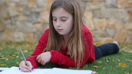 lefekvés : Blond kid girl maths homework laying on grass counting fingers With writing in notebook