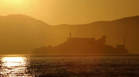 используемый : Alcatraz island penitentiary at sunset and backlit in San Francisco