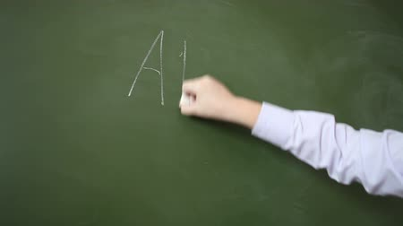мел : Hand schoolboy writes with chalk on a blackboard