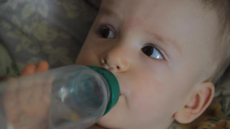 nipple : baby drinks juice from a bottle, close-up portrait