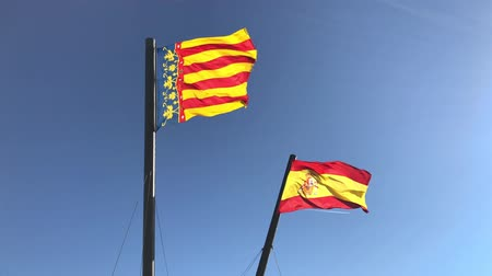 Flags of Spain and the autonomous community of Valencia waving in the wind against clear blue sky background