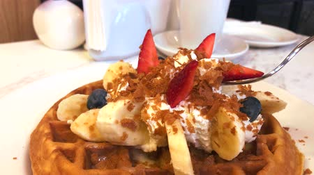 belga : Eating homemade waffles on a white plate with strawberries, banana and blueberries Stock Footage