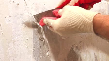 scrape : Video of hands in gloves removing of old wallpaper with spatula