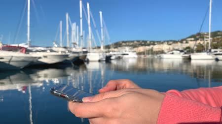 FRANCE, CANNES - JANUARY 10, 2019: Girl in pink sweatshirt against white background holding IPhoneX, texting, typing, swiping
