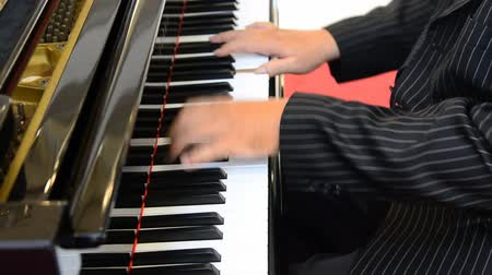 Hand of male hands playing piano .