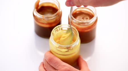 condensed : Stirring milk caramel sauce with a spoon in glass jar. Homemade fruit caramel sauce Stock Footage