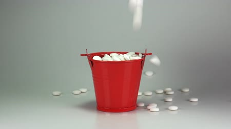 nutritional supplement : Pills dropped in red bucket. 4K