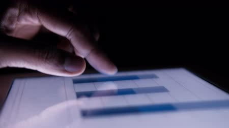 dikkatli inceleme : Close up of man hand analyzing chart on digital tablet at night Stok Video